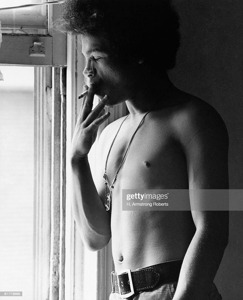 Shirtless Hispanic man with afro, standing by window, smoking. : Bildbanksbilder
