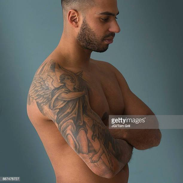 Shirtless Hispanic man with tattoos