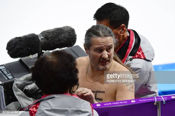 A shirtless man clad in a tutu is escorted off the rink following the men's 1000m speed skating event medal ceremony during the Pyeongchang 2018...
