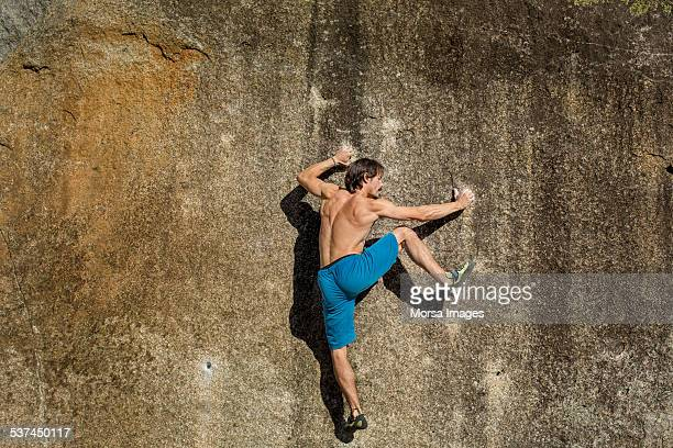 Shirtless man climbing on rock