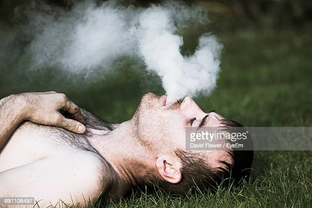 shirtless man exhaling smoke while lying on field - female hairy chest stock pictures, royalty-free photos & images
