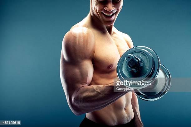 Hombre sin camisa sosteniendo una pesa