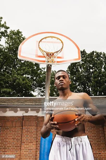 shirtless man holding basketball