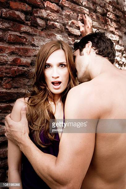 Shirtless Man Holding Surprised Woman Near Brick Wall