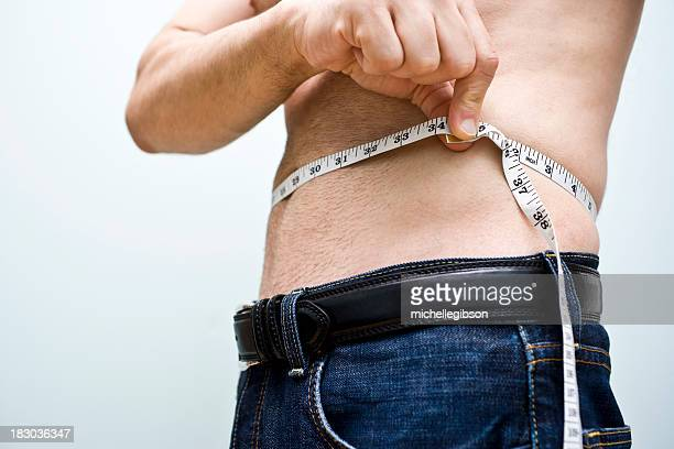 shirtless man measuring his waist with a measuring tape - underweight stock photos and pictures