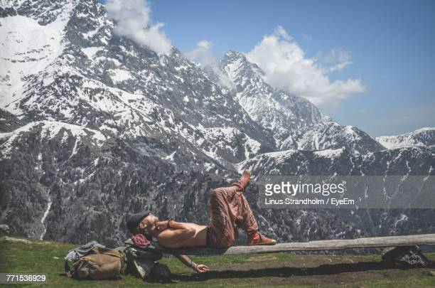 shirtless man relaxing on bench against snowcapped mountain against sky - halbbekleidet stock-fotos und bilder