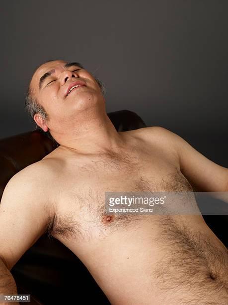 shirtless man relaxing - hairy chest stock-fotos und bilder