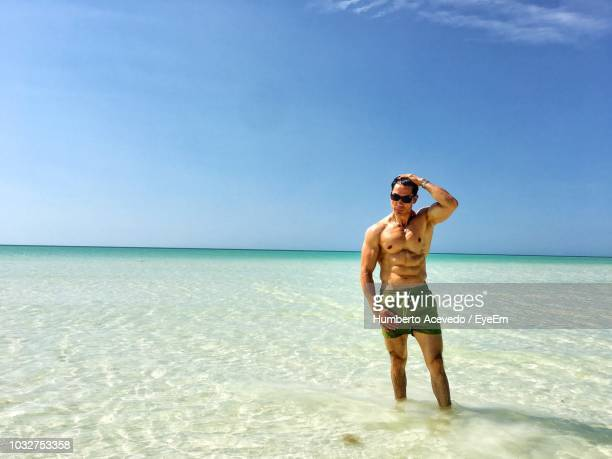 Shirtless Man Standing In Sea On Sunny Day