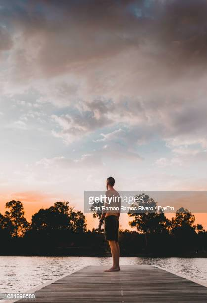 Shirtless Man Standing On Pier Over Lake Against Sky During Sunset