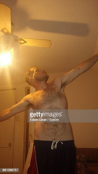 shirtless man standing with arms outstretched in illuminated room - female hairy chest stock pictures, royalty-free photos & images