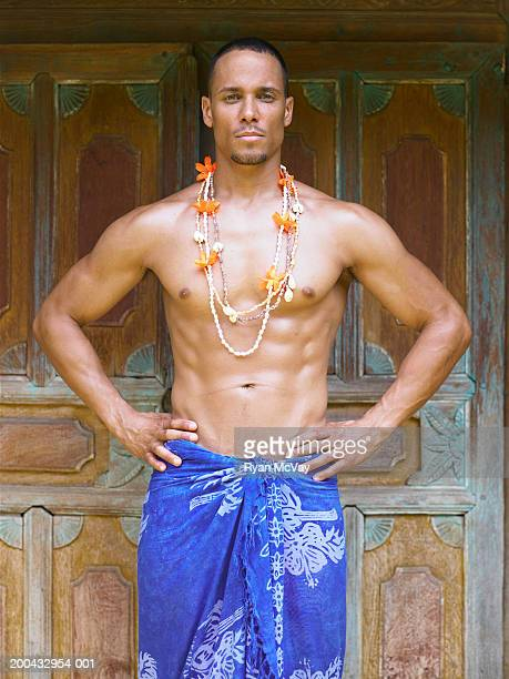 Shirtless man wearing sarong, hands on hips, portrait