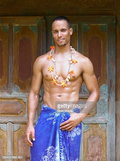 Shirtless man wearing sarong, smiling, portrait