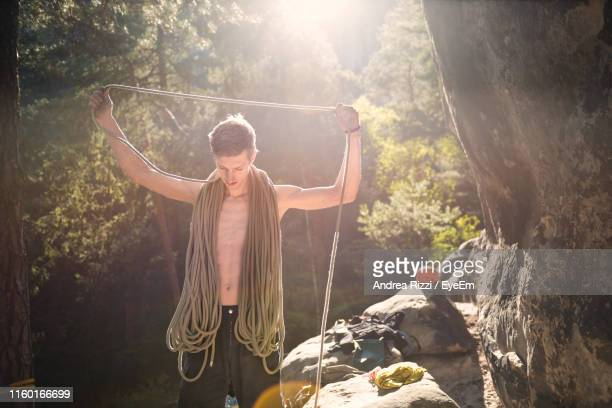Shirtless Man With Climbing Ropes Standing In Forest