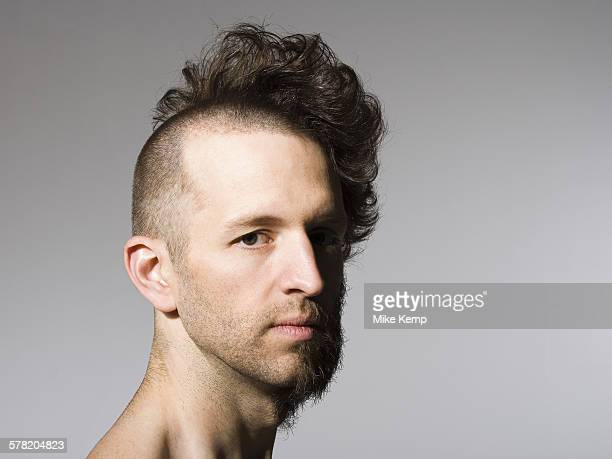 Shirtless man with half shaved hair and beard