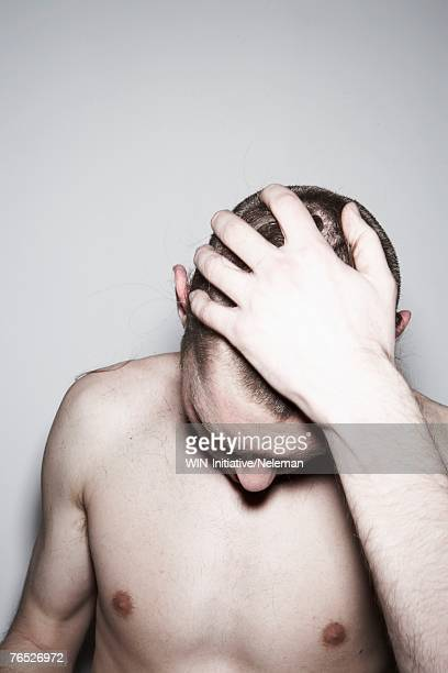 Shirtless man with hand in hair