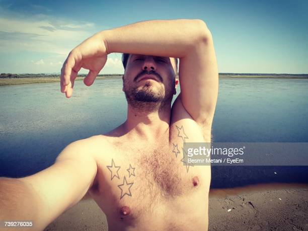 Shirtless Man With Star Shape Tattoo Standing At Sea Shore During Sunny Day