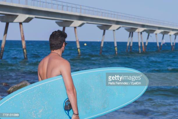 Shirtless Man With Surfboard At Beach