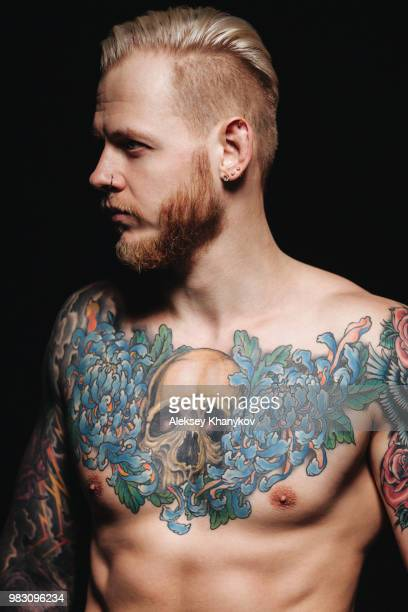 A shirtless man with tattoos.