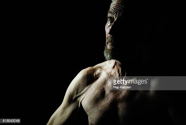 A shirtless mature man looking up in contemplation