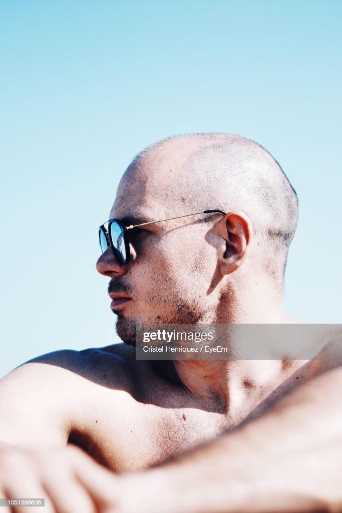 81a03f204ec2 Shirtless Mid Adult Man Wearing Sunglasses While Sitting At Beach Against  Clear Sky During Sunny Day