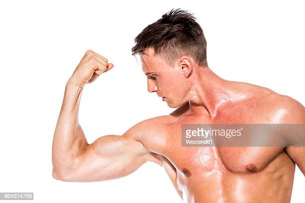 Shirtless muscular man flexing his biceps in front of white background