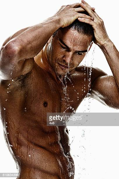 Shirtless muscular man having shower