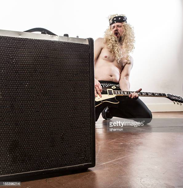 Shirtless Rockstar Kneeling With Guitar Amplifier in Foreground White Background