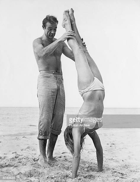 Shirtless Scottish actor Sean Connery holds Swiss actor Ursula Andress while she does a handstand on a beach in a white bikini on the set of the film...