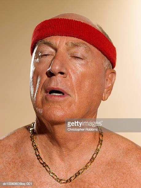 Shirtless senior man wearing headband and gold chain, eyes shut