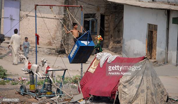 A shirtless slum dwelling boy takes a ride on a swing as they lead life in poverty and unhealthy conditions in Islamabad Pakistan on September 19...
