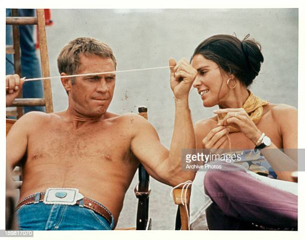 A shirtless Steve McQueen sitting next to Ali MacGraw on the set of the film 'The Getaway' 1972