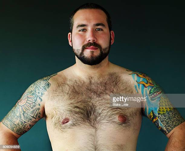 shirtless tattooed man hands on hips - hairy chest stock-fotos und bilder