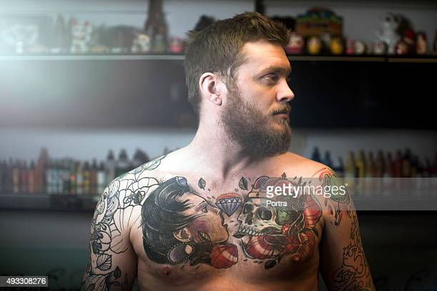 Shirtless tattooed man looking away in studio