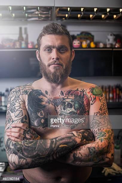 Shirtless tattooed man standing arms crossed in studio