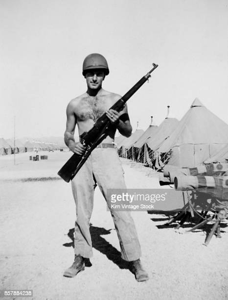 A shirtless US Army soldier holds his rifle at Fort Francis E Warren training camp in Wyoming