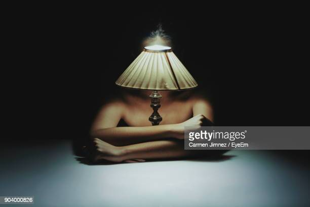 Shirtless Woman Sitting With Illuminated Lamp On Table In Darkroom