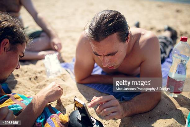 Shirtless young man adjusts a playlist on his iPhone on the sunny beach.