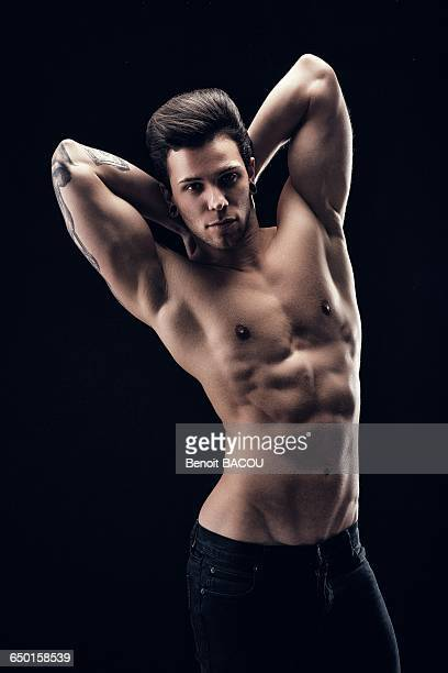 Shirtless young man, face, hands behind head