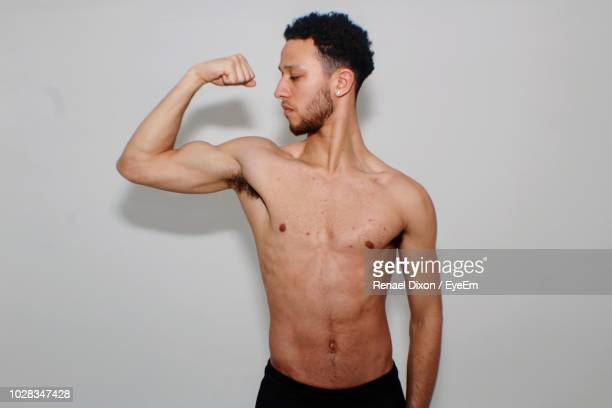 shirtless young man flexing muscles against white background - muskel stock-fotos und bilder