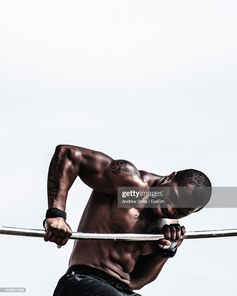 Shirtless Young Man Lifting Weights While Standing Against White Background : Stock Photo