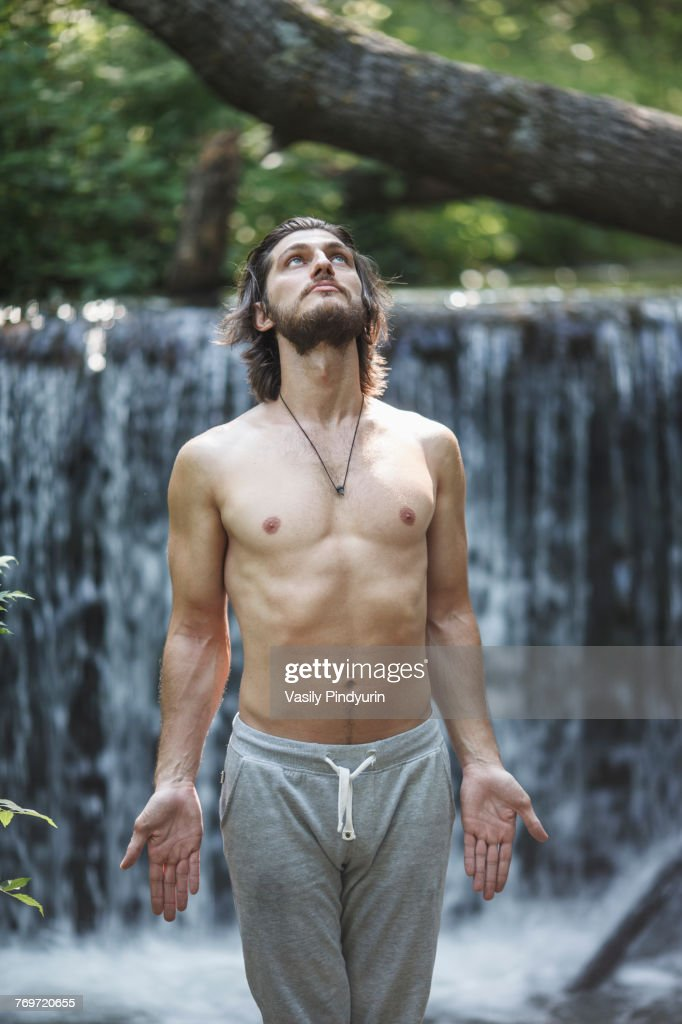 Shirtless young man looking up while standing against waterfall at forest : Foto de stock