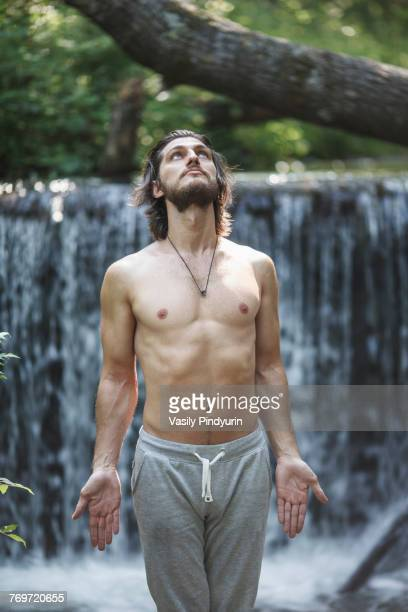 shirtless young man looking up while standing against waterfall at forest - hands in her pants fotografías e imágenes de stock