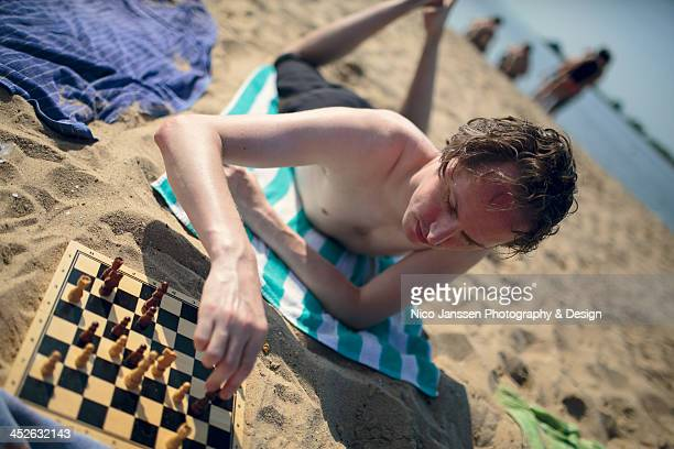 Shirtless young man playing a game of chess in the sand on the beach in late summer.