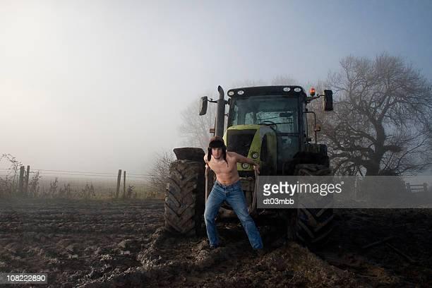 Torse nu jeune homme tirant tracteur sur champ de Foggy Bottom