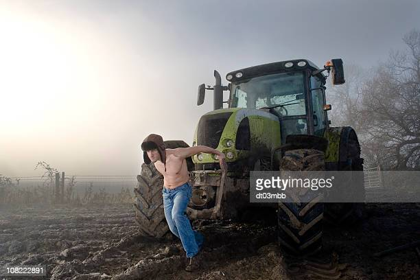 Shirtless Young Man Pulling Tractor on Foggy Field