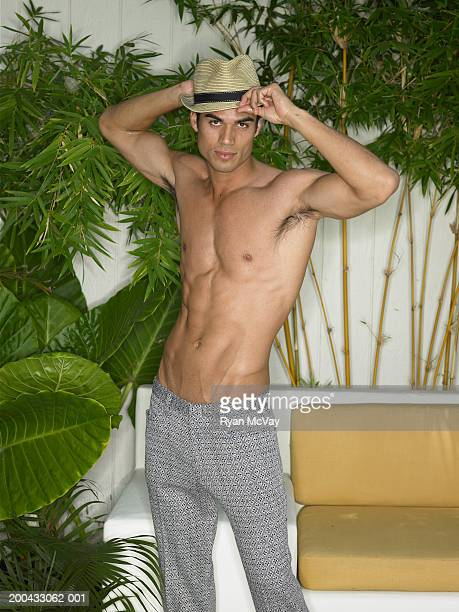 Shirtless young man tipping hat, portrait