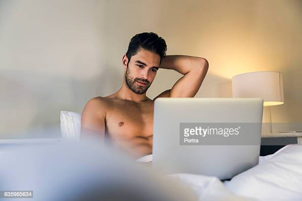 shirtless young man using laptop in bed - a petto nudo foto e immagini stock