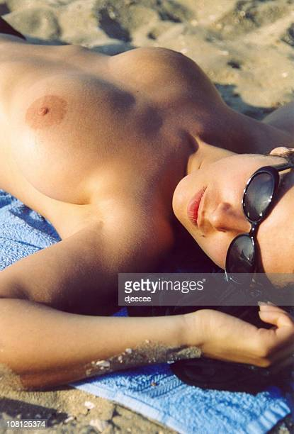 Shirtless Young Woman Lying on Beach Towel in Sand