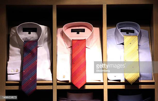 Shirts and ties sit on display at the Gieves Hawkes store owned by Trinity Ltd on Saville Row in London UK on Tuesday Aug 7 2012 UK retail sales rose...
