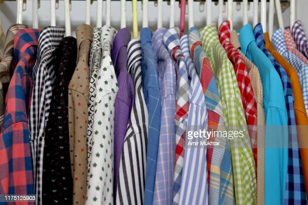 shirts hanging on hangers in closet - printed sleeve stock pictures, royalty-free photos & images